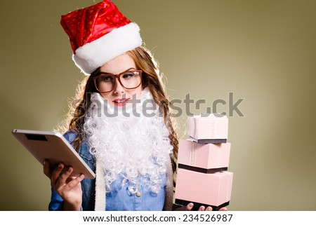 Funny hipster girl in super size eyeglasses wearing xmas santa hat and faux beard holding three boxes of presents and tablet pc over olive copy space background  - stock photo
