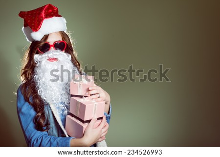Funny hipster girl in super size heart shape sunglasses wearing xmas santa hat and faux beard holding three boxes of presents over olive copy space background  - stock photo
