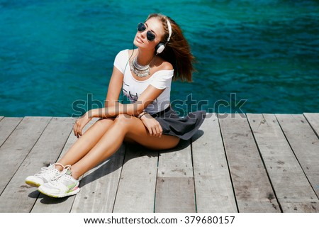 Funny Hipster Girl in urban street,hipster outfit Going Crazy at tropical island,windy day Background.Trendy Casual Fashion Outfit in summer,spring.Toned Photo,Copy Space.music on cool big headphones - stock photo