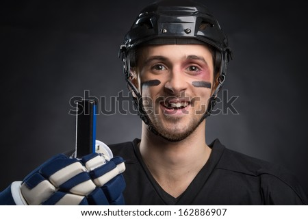 Funny hockey player smiling with one tooth missing. Isolated on black  - stock photo