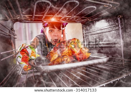 Funny Housewife overlooked roast chicken in the oven, so she had scorched (focus on chicken), view from the inside of the oven. Housewife perplexed and angry. Loser is destiny! Thanksgiving Day. - stock photo