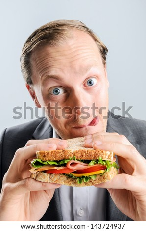Funny humourous man eating a sandwich with exagerrated wide eye comical expression and sticking his tongue out - stock photo