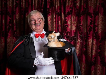 Funny illusionist on stage with a rabbit in his top hat - stock photo