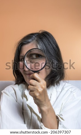 Funny image of a adult woman with a magnifying glass, one eye is enlarged.  - stock photo