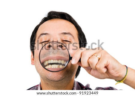 Funny image of a man with magnifying glass held up to face enlarging mouth and teeth. - stock photo