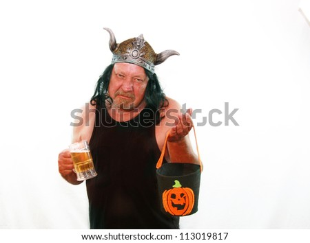Funny image of grumpy older man with viking cap, halloween trick-or-treat bag and mug of beer, isolated on white. - stock photo