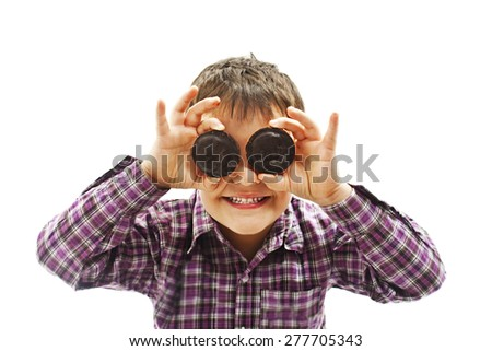 Funny image of little boy showing chocolate biscuit. Isolated on white background   - stock photo