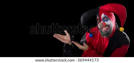 funny Jester showing to copyspace, concept halloween and horror, black background - stock photo