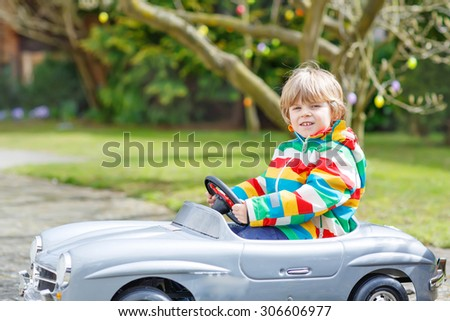 Funny kid boy driving big toy old vintage car and having fun, outdoors. Active leisure with kids outdoors  on warm spring or autumn day. - stock photo