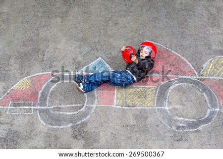 Funny kid boy having fun with race car picture drawing with colorful chalks. Creative leisure for children outdoors in summer - stock photo
