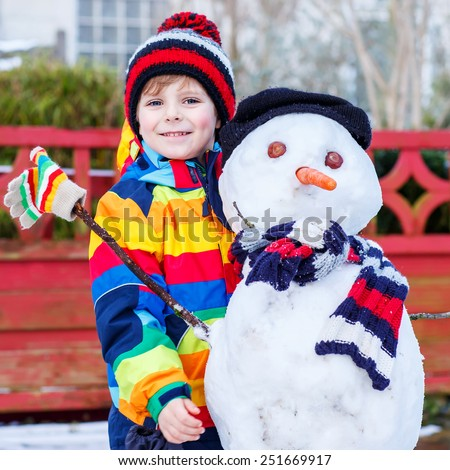 Funny kid boy in colorful clothes making a snowman, playing and having fun with snow, outdoors  on cold day. Active outoors leisure with children in winter. - stock photo