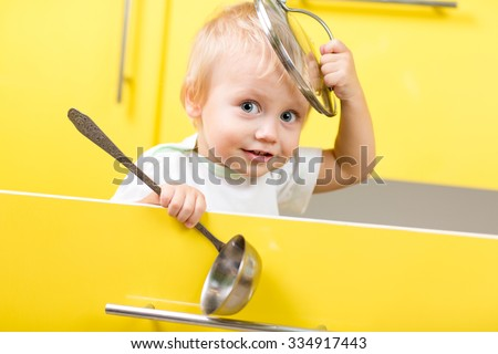 Funny kid boy sitting inside yellow opened kitchen box with laddle - stock photo