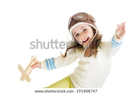 funny kid dressed as pilot and playing with wooden airplane toy isolated on white background - stock photo
