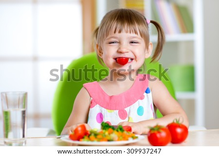 funny kid girl eating healthy food vegetables at home - stock photo