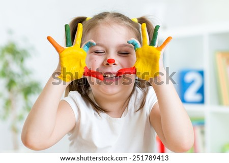 funny kid girl playing with color paints indoor - stock photo