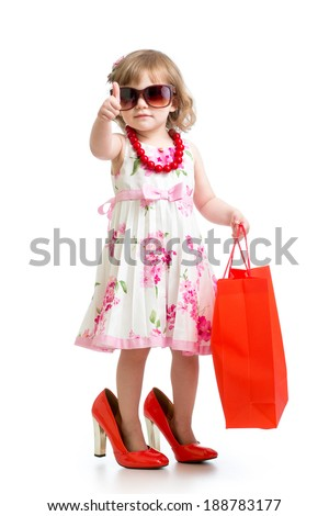 Funny kid girl trying on her mom's red accessories and shoes - stock photo