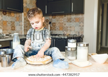Funny kid sitting on the kitchen table in a rustic kitchen playing with flour and tasting a cake. He is covered in flour and looks funny. He is cute. Milk and different jars stand on the table. - stock photo