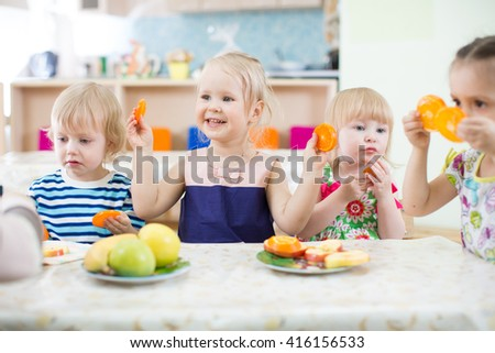 Funny kids eating fruits in day care centre - stock photo