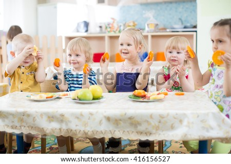 Funny kids eating fruits in kindergarten or day care centre - stock photo