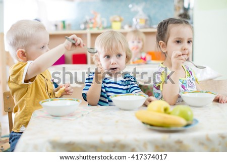 Funny kids group eating in kindergarten - stock photo