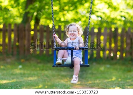 Funny laughing baby girl having fun on a swing ride at a playground in a sunny summer park - stock photo