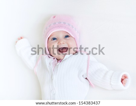 Funny laughing baby girl in a white knitted sweater and a warm pink hat relaxing on a white blanket - stock photo