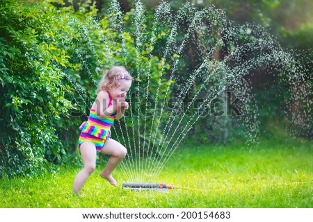 Funny laughing little girl in a colorful swimming suit running though garden sprinkler playing with water splashes having fun in the backyard on a sunny hot summer vacation day  - stock photo