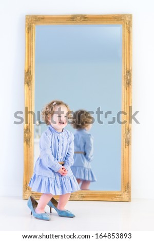 Funny laughing toddler girl with beautiful curly hair wearing a blue dress is trying on her mother's elegant high heels shoes standing in front of a big mirror with wooden frame in a white bedroom  - stock photo