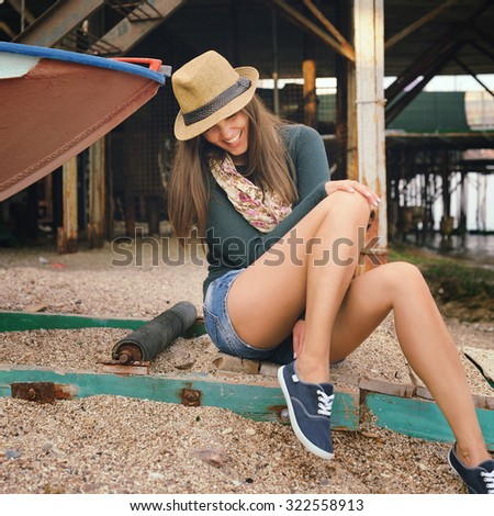 Funny laughing young woman with long legs looking on her gumshoes under the old pier, autumn outdoor. - stock photo