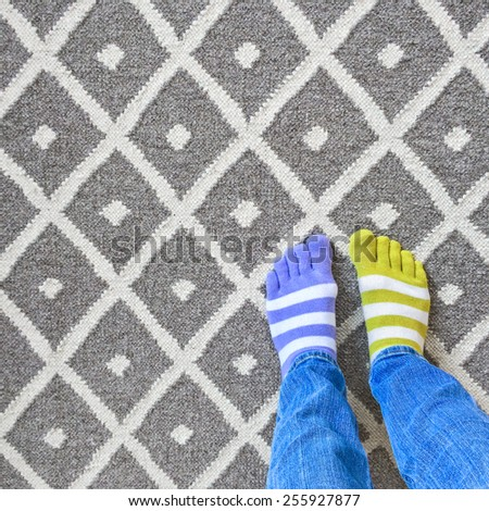 Funny legs in mismatched socks on gray carpet. - stock photo
