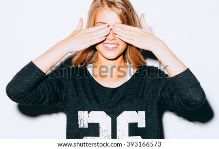 Funny lifestyle portrait beautiful blond crazy girl closes eyes with her hands , in Sweatshirt and white shorts, having fun, emotional and happy mood. Close up. Indoor. Warm color. Hipster. - stock photo