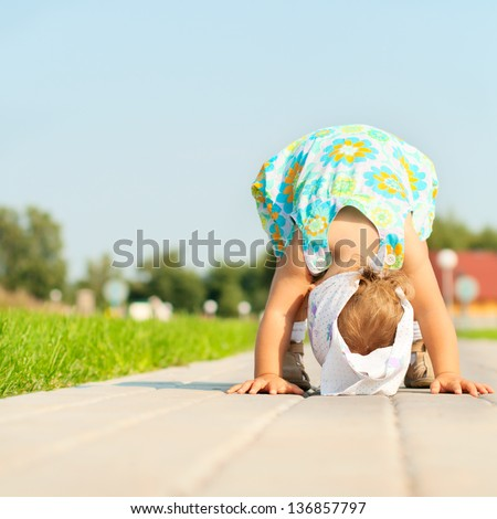 Funny little baby girl standing on hands outdoors - stock photo