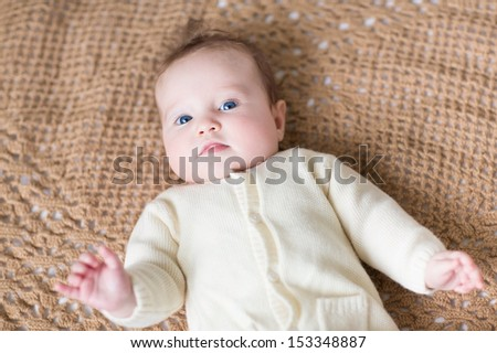 Funny little baby in a warm sweater playing on a brown knitted blanket - stock photo