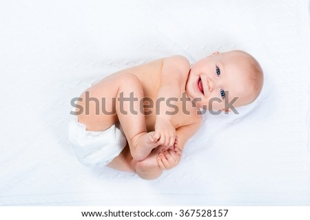 Funny little baby wearing a diaper playing on a white knitted blanket in a sunny nursery. Child after bath or shower on a fresh towel. Infant nappy change and skin care. Cute kid playing with his feet - stock photo