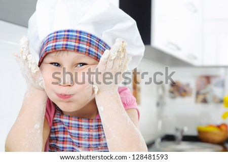 Funny little baker grimaces in the kitchen - stock photo
