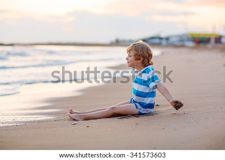 Funny little blond kid boy having fun with building sand castle on the beach of ocean or see by sunset. Happy child spending active vacations. - stock photo