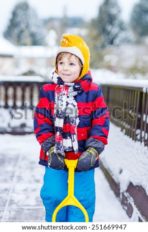Funny little boy boy in colorful clothes happy about snow, playing and having fun, outdoors during snowfall on cold day. Active outoors leisure with children in winter. - stock photo