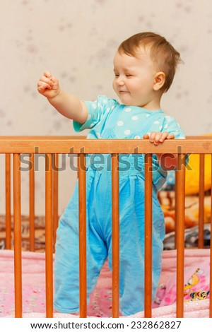 Funny little boy dancing in bed - stock photo