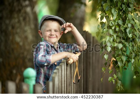 funny little boy in a cap and a bully with a slingshot in his hands - stock photo