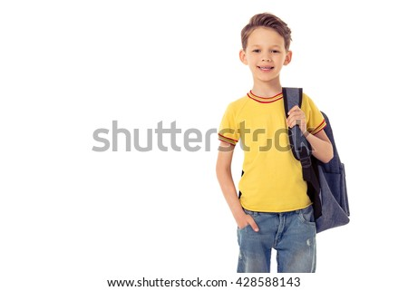 Funny little boy is looking at camera and smiling while standing with school backpack, isolated on a white background - stock photo