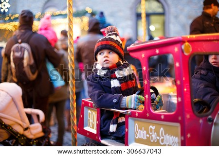 Funny little boy on a carousel at Christmas funfair or market, outdoors. Happy child having fun. Traditional xmas market in Germany, Europe. Holiday, children, lifestyle concept. - stock photo