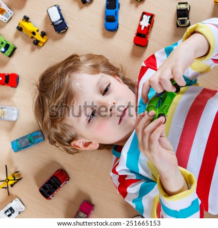Funny little boy playing with lots of toy cars indoor. Kid boy wearing colorful shirt and having fun. - stock photo