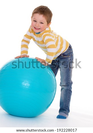 Funny little boy plays with big blue ball, isolated on white background - stock photo