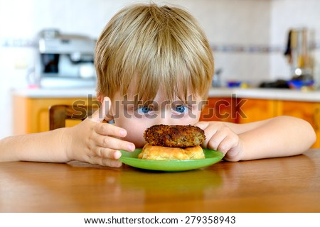 Funny little boy with cutlet in the kitchen - stock photo