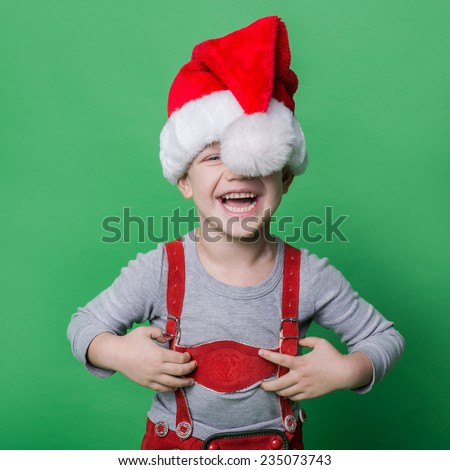 Funny little boy with Santa Claus hat laugh. Christmas concept. Studio portrait over green background - stock photo