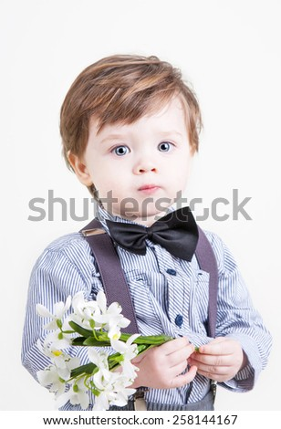 Funny little boy with snowdrops in hand  smiles - stock photo