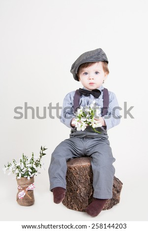 Funny little boy with snowdrops in hands sitting on a stump and smiling - stock photo