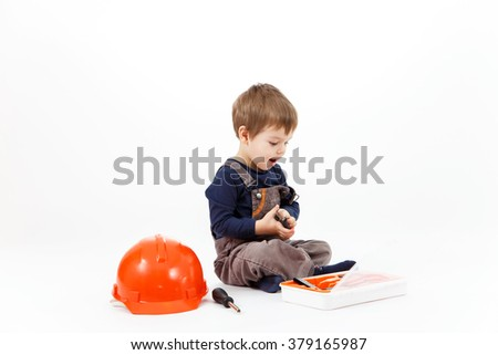 Funny little boy with tools kit on white background - stock photo