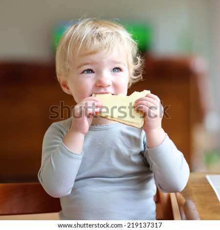 Funny little child, blonde toddler girl, sitting on high feeding chair in the kitchen eating sandwich, bread with butter and cheese, for breakfast on a sunny morning - stock photo