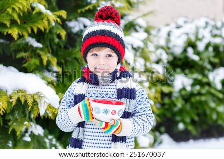 Funny little child holding big cup with snowflakes and hot cocoa and chocolate drink and marshmallows. Kid boy in winter sweater, hat, long warm scarf and colorfull gloves. On cold snowy winter day. - stock photo